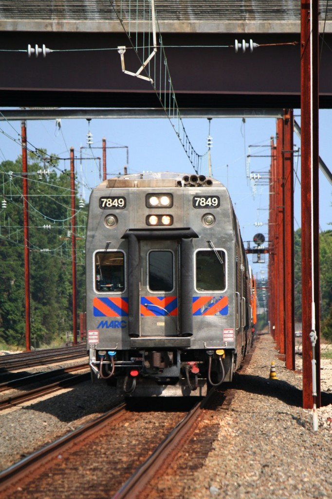 A cab car leads a mid day train into the station for its first stop.