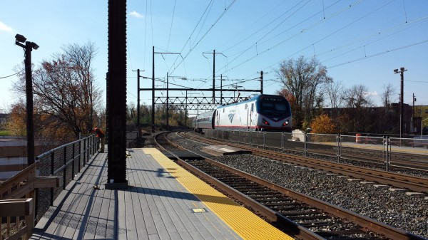 A northbound ACS64 leads a passenger train past the West Baltimore MARC station.