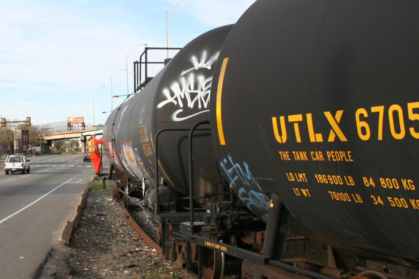 The conductor guides the shove move from the end of the first tank car.